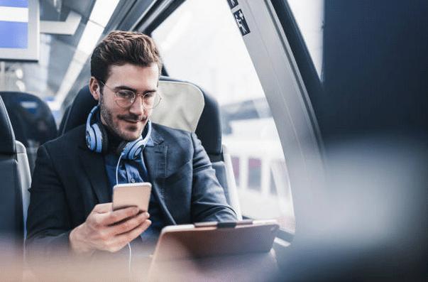 Homme avec un portable et une tablette, assis dans un transport en commun